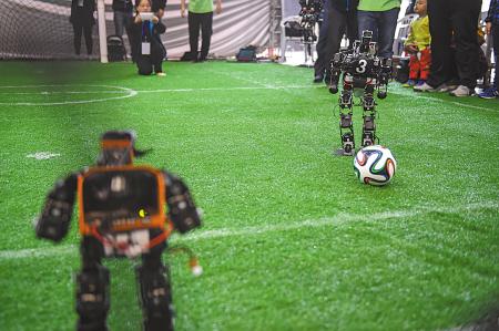 RoboCup类人组决赛现场操控机器人进行足球赛.-宁波日报社数字报