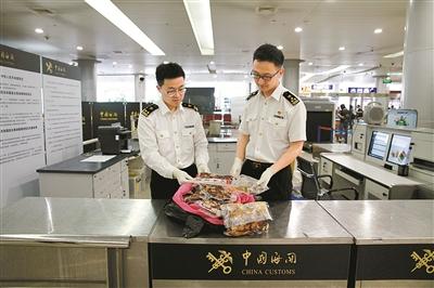 宁波海关关员正在对截获的肉类制品进行查验.(姚黎 董娜 摄)