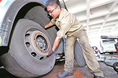 修理工俞经伟正在更换387路公交车破损的轮胎.(张燕 董美巧 摄)