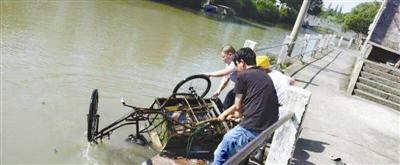 眾人合力撈起落水者的三輪車.圖片